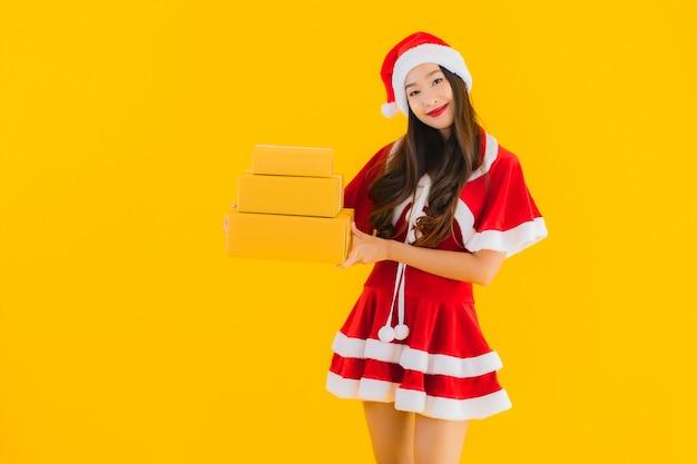 Portret piękna młoda azjatykcia kobieta nosi świąteczne ubrania kapelusz z paczką