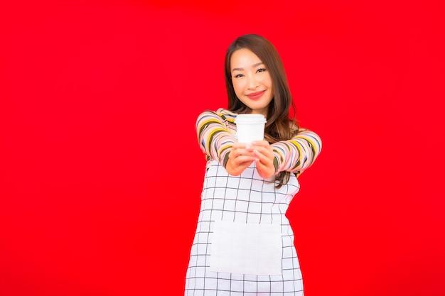 Portret piękna młoda azjatykcia kobieta nosić fartuch z filiżanką kawy na czerwonej ścianie