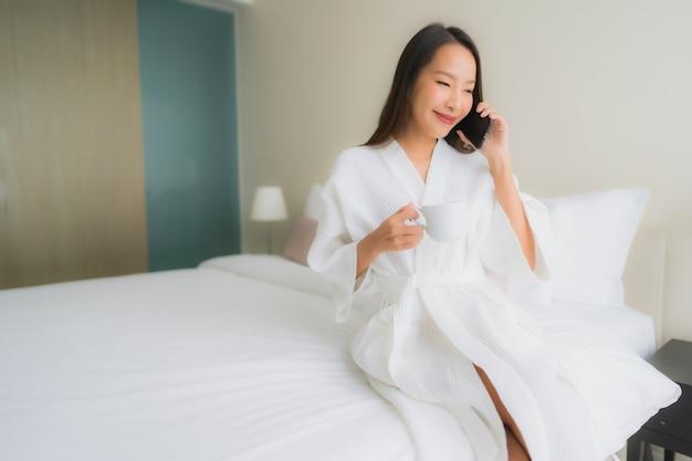 Portret piękna młoda azjatykcia kobieta pije kawę i opowiada na telefonie