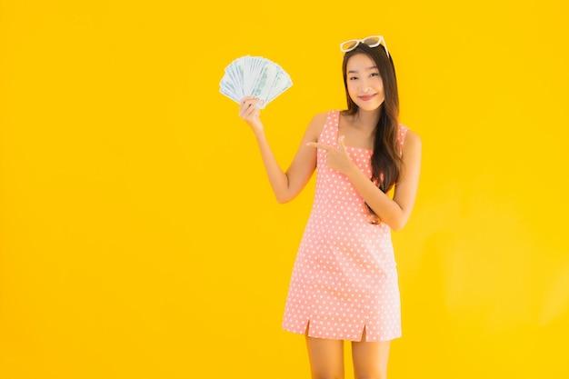Portret piękna młoda azjatykcia kobieta pokazuje dużo gotówkę i pieniądze