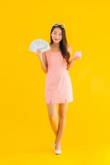 Portret piękna młoda azjatykcia kobieta pokazuje dużo gotówkę lub pieniądze z prosiątko bankiem