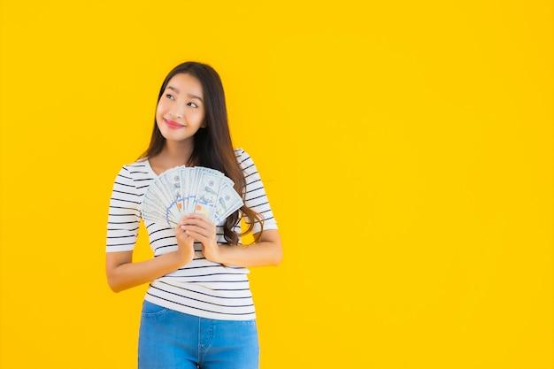 Portret piękna młoda azjatykcia kobieta pokazuje mnóstwo dolara gotówkę lub pieniądze