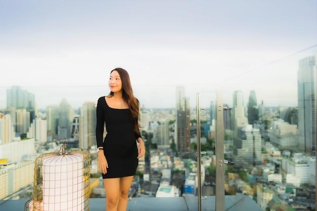 Portret piękna młoda azjatykcia kobieta przy dach restauracją i barem