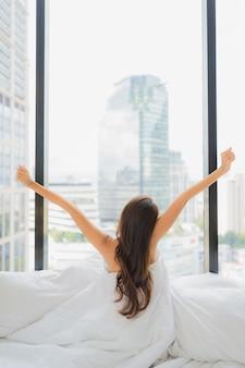 Portret piękna młoda azjatykcia kobieta relaks na łóżku z widokiem na miasto