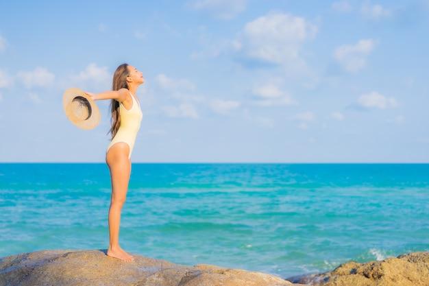 Portret piękna młoda azjatykcia kobieta relaks uśmiech wypoczynek wokół plaży oceanu morskiego na wycieczkę wakacyjną