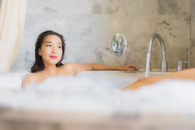 Portret piękna młoda azjatykcia kobieta relaksuje kąpieli