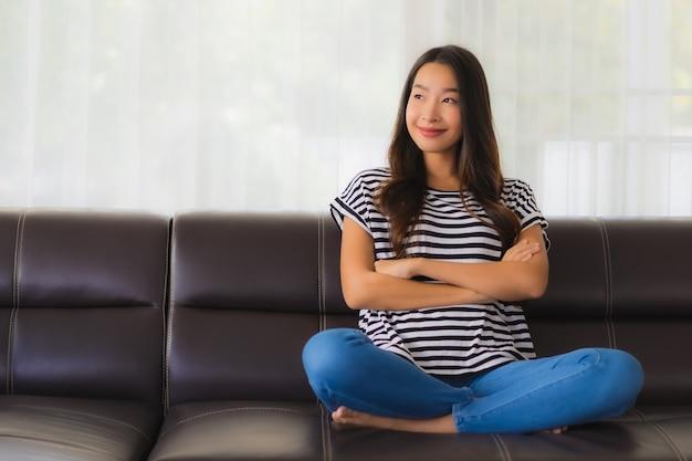 Portret piękna młoda azjatykcia kobieta relaksuje na kanapie w żywym pokoju