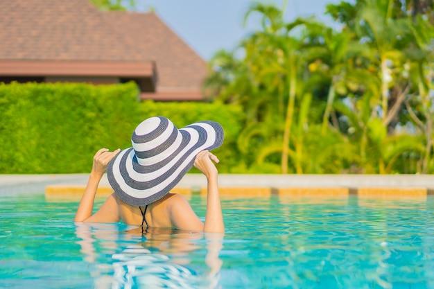Portret piękna młoda azjatykcia kobieta relaksuje się wokół basenu w hotelu na wakacjach