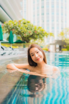 Portret piękna młoda azjatykcia kobieta relaksuje szczęśliwego uśmiechu czas wolnego wokoło plenerowego pływackiego basenu