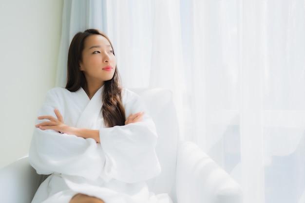 Portret piękna młoda azjatykcia kobieta relaksuje szczęśliwy uśmiech z filiżanką kawy na kanapie