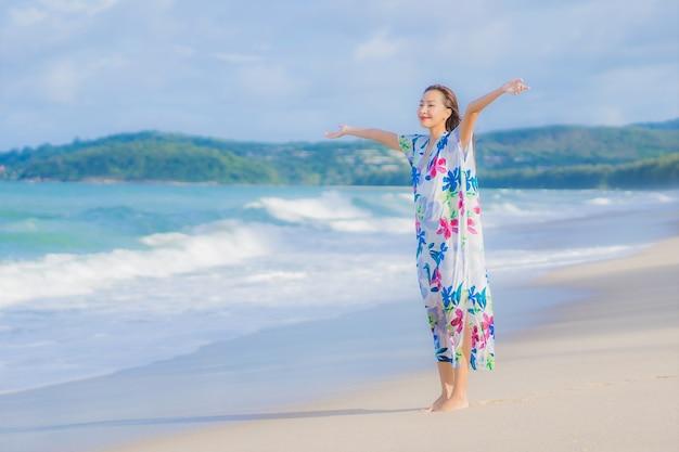 Portret piękna młoda azjatykcia kobieta relaksuje uśmiech wokół plaży i oceanu w wakacje wakacje