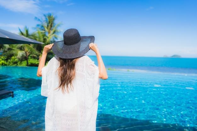 Portret piękna młoda azjatykcia kobieta relaksuje w luksusowym plenerowym pływackim basenie w hotelowego kurortu prawie plażowym dennym oceanie