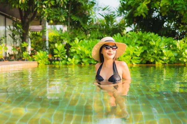 Portret piękna młoda azjatykcia kobieta relaksuje w pływackim basenie przy hotelowym kurortem dla czasu wolnego wakacje