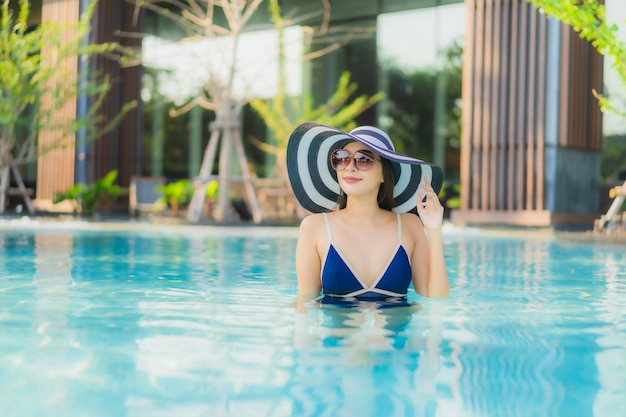 Portret piękna młoda azjatykcia kobieta relaksuje w pływackim basenie w hotelowym kurorcie