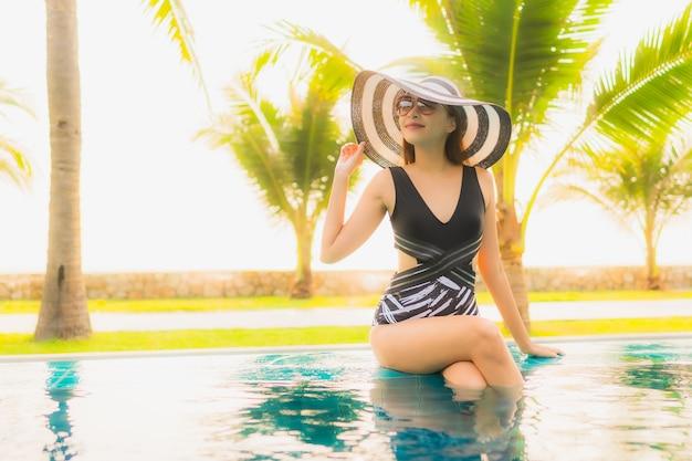 Portret piękna młoda azjatykcia kobieta relaksuje wokoło plenerowego pływackiego basenu w hotelowym kurorcie z drzewkiem palmowym przy zmierzchem lub wschodem słońca