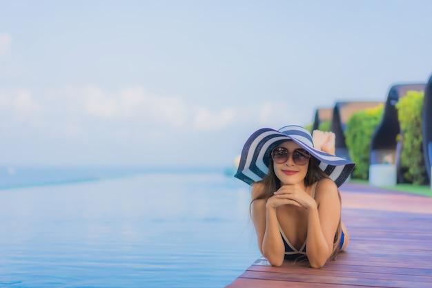 Portret piękna młoda azjatykcia kobieta relaksuje wokoło pływackiego basenu w hotelowym kurorcie