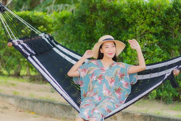 Portret piękna młoda azjatykcia kobieta siedzi na hamaku huśtawka wokół oceanu plaży na wakacjach