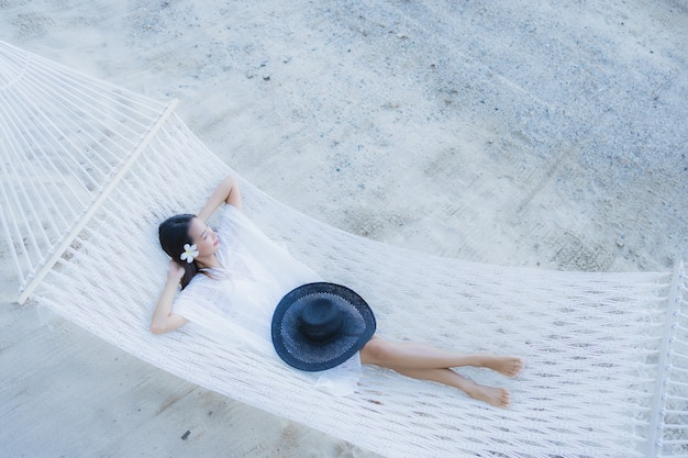 Portret piękna młoda azjatykcia kobieta siedzi na hamaku wokoło dennej plaży oceanu dla relaksu