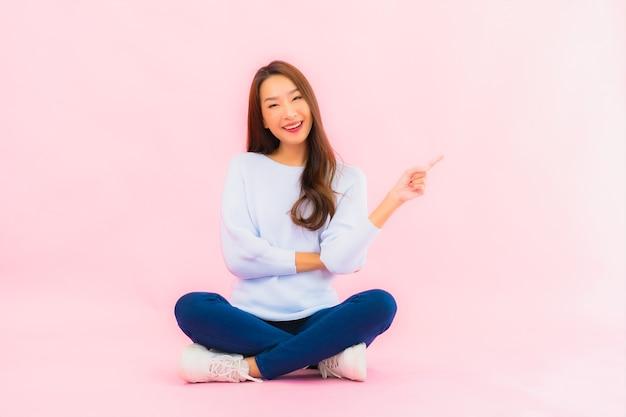 Portret piękna młoda azjatykcia kobieta siedzi na podłodze z różową ścianą na białym tle