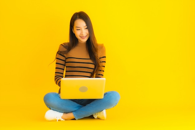 Portret piękna młoda azjatykcia kobieta siedzi na podłoga dla use laptopu lub komputeru na kolor żółty ścianie