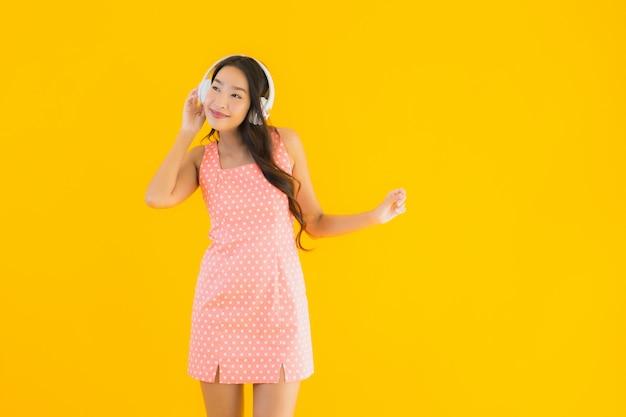 Portret piękna młoda azjatykcia kobieta słucha muzykę z hełmofonem