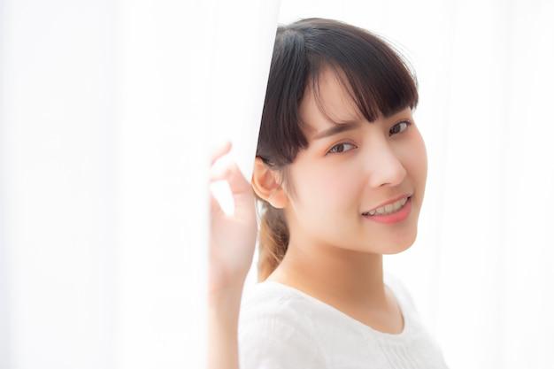 Portret piękna młoda azjatykcia kobieta stoi uśmiech i okno
