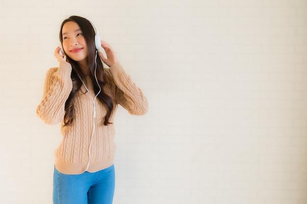 Portret piękna młoda azjatykcia kobieta szczęśliwa cieszy się z słucha muzykę
