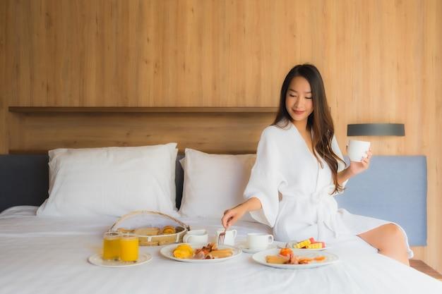 Portret piękna młoda azjatykcia kobieta szczęśliwa cieszy się z śniadaniem na łóżku w sypialni