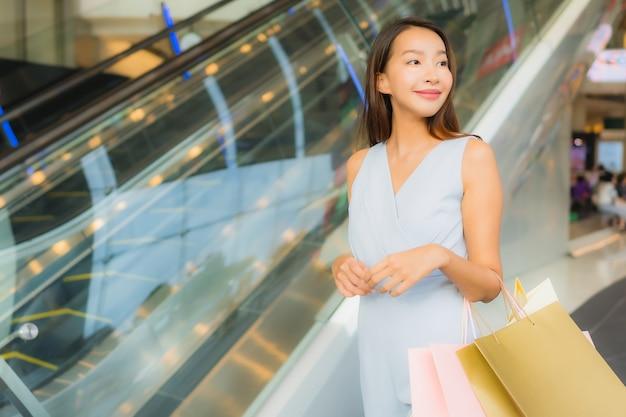 Portret piękna młoda azjatykcia kobieta szczęśliwa i uśmiech z torba na zakupy od wydziałowego sklepu