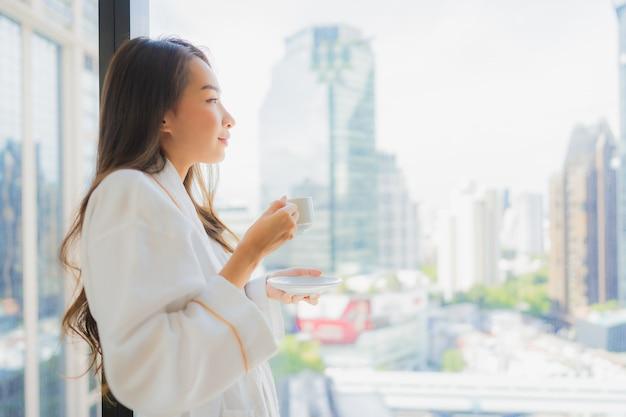 Portret piękna młoda azjatykcia kobieta trzyma filiżankę kawy z widokiem na miasto