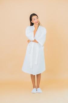 Portret piękna młoda azjatykcia kobieta ubrana w szlafrok z uśmiechem na beżu