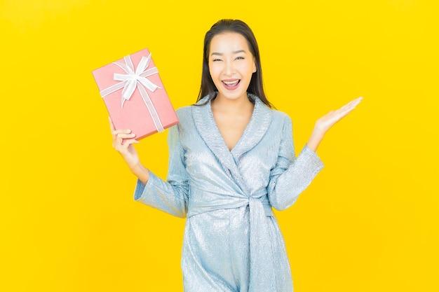 Portret piękna młoda azjatykcia kobieta uśmiech z czerwonym pudełkiem na żółtej ścianie