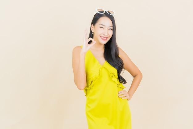 Portret piękna młoda azjatykcia kobieta uśmiech z działaniem na kremowej ścianie
