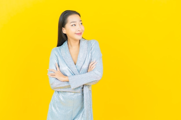 Portret piękna młoda azjatykcia kobieta uśmiech z działaniem na żółtej ścianie
