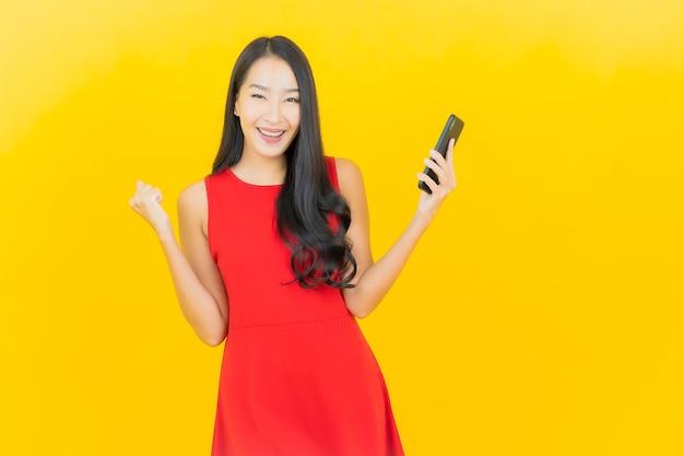 Portret piękna młoda azjatykcia kobieta uśmiech z inteligentny telefon komórkowy na żółtej ścianie