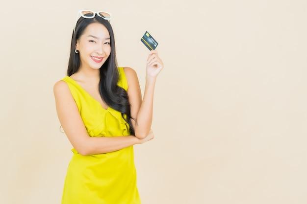 Portret piękna młoda azjatykcia kobieta uśmiech z kartą kredytową na kolorowej ścianie