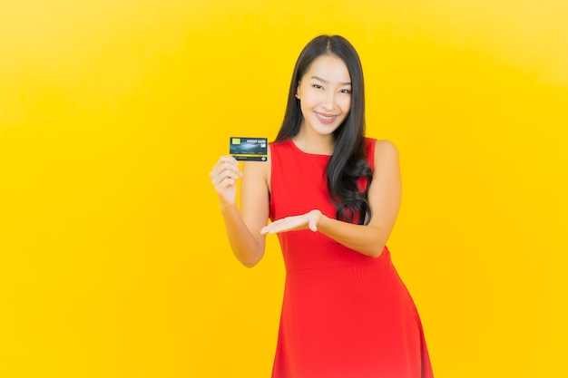 Portret piękna młoda azjatykcia kobieta uśmiech z kartą kredytową na żółtej ścianie