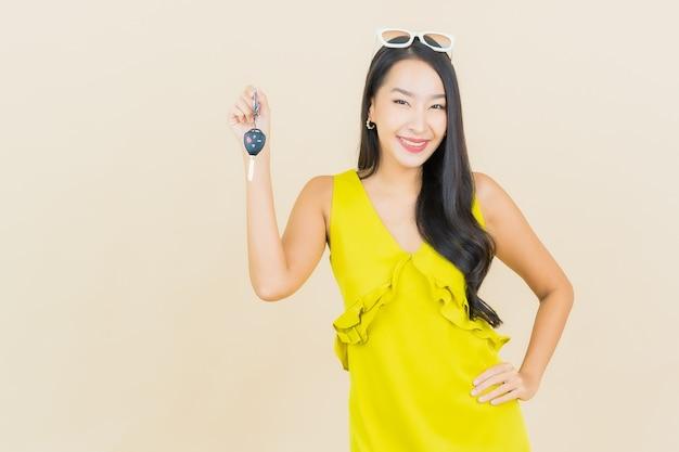 Portret piękna młoda azjatykcia kobieta uśmiech z kluczyk na ścianie koloru