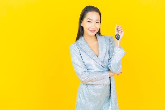 Portret piękna młoda azjatykcia kobieta uśmiech z kluczyk na żółtej ścianie