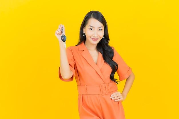 Portret piękna młoda azjatykcia kobieta uśmiech z kluczyk na żółto