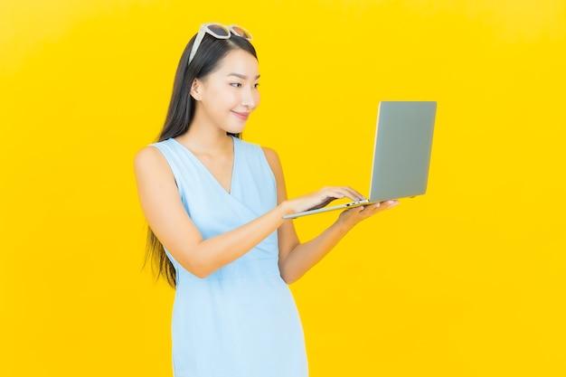 Portret piękna młoda azjatykcia kobieta uśmiech z komputerowym laptopem na żółtej ścianie na białym tle