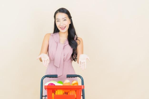 Portret piękna młoda azjatykcia kobieta uśmiech z koszykiem z supermarketu