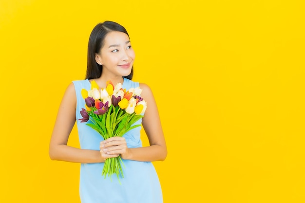 Portret piękna młoda azjatykcia kobieta uśmiech z kwiatem na żółtej ścianie