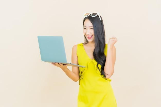 Portret piękna młoda azjatykcia kobieta uśmiech z laptopa na odosobnionej ścianie