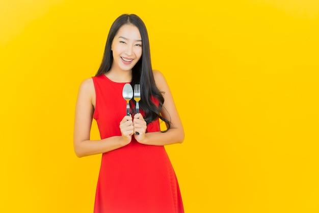 Portret piękna młoda azjatykcia kobieta uśmiech z łyżką i widelcem na żółtej ścianie