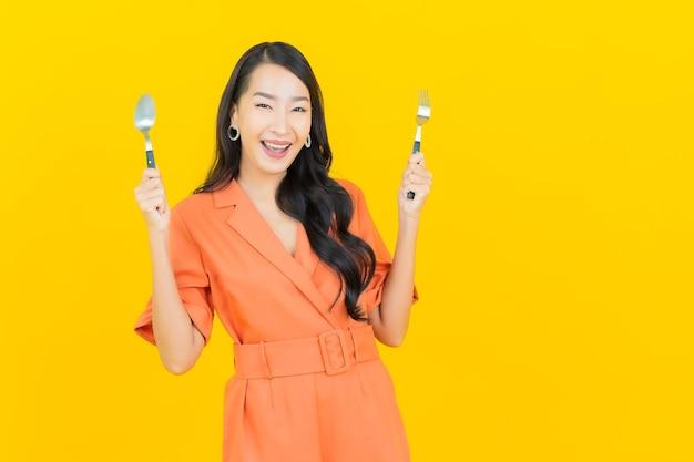 Portret piękna młoda azjatykcia kobieta uśmiech z łyżką i widelcem na żółto