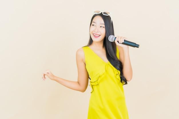 Portret piękna młoda azjatykcia kobieta uśmiech z mikrofonem do śpiewania na ścianie