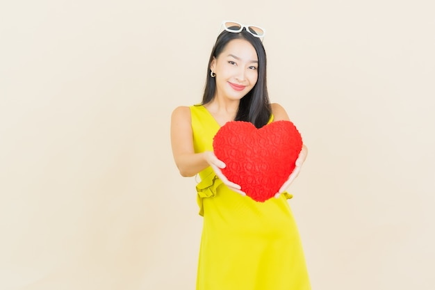 Portret piękna młoda azjatykcia kobieta uśmiech z poduszką w kształcie serca na ścianie koloru