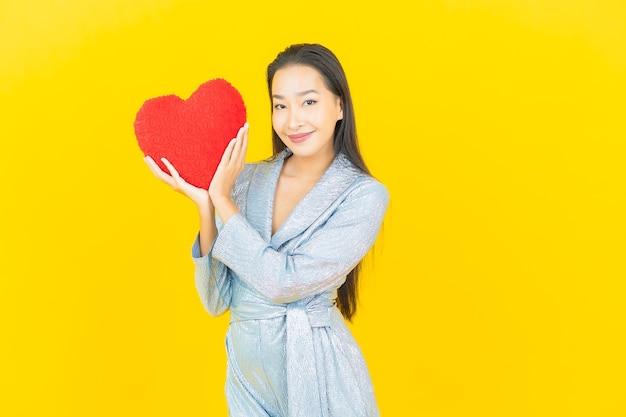 Portret piękna młoda azjatykcia kobieta uśmiech z poduszką w kształcie serca na żółtej ścianie