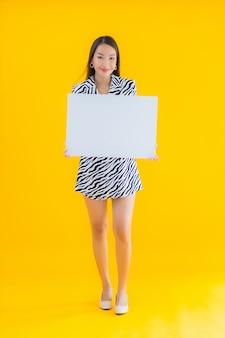 Portret piękna młoda azjatykcia kobieta uśmiech z pustym białym billboardem na żółtym tle
